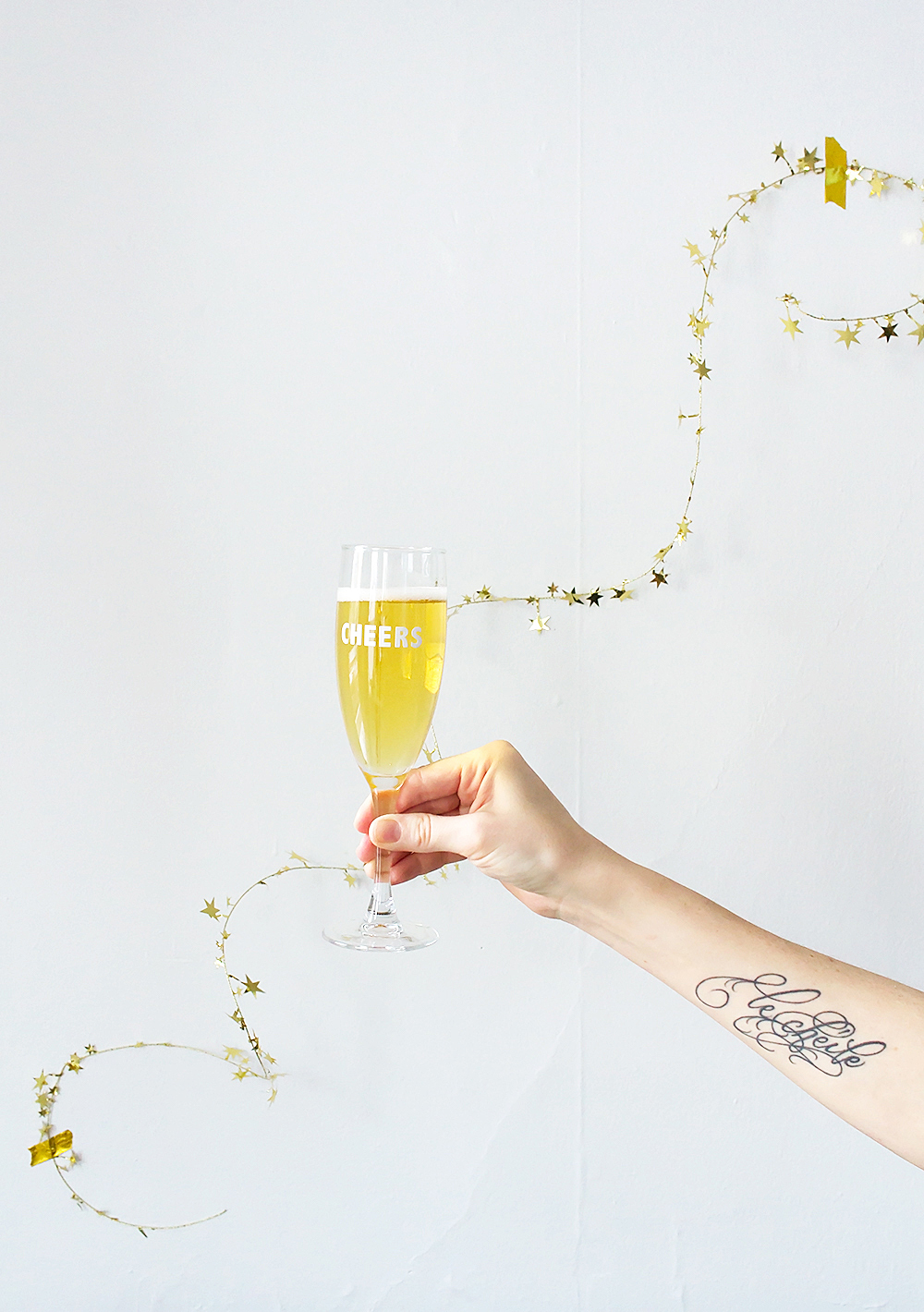 Get festive with this 5 minute New Year's Eve party hack. These DIY Cheers Champagne Flutes are super quick, and all you need are stickers!