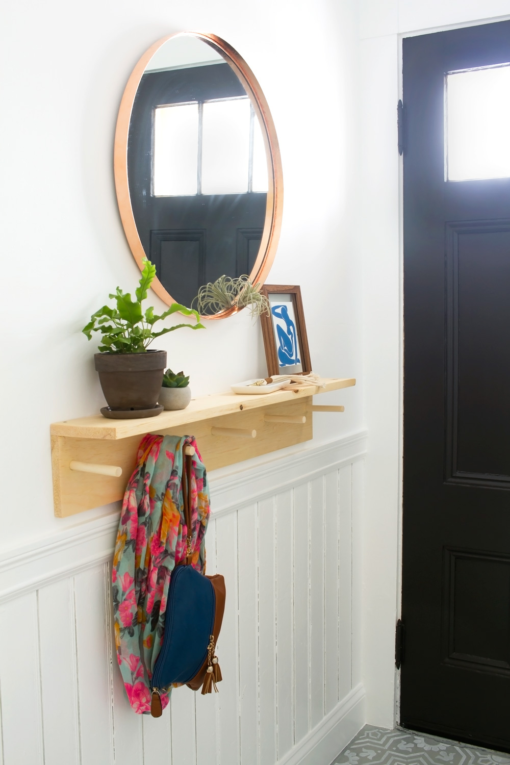 This minimal DIY entryway coat rack is simple to make with a power drill and just a few supplies. Dowel pegs can hold your bags and jackets and a shelf can catch your keys and provide a spot for decoration!